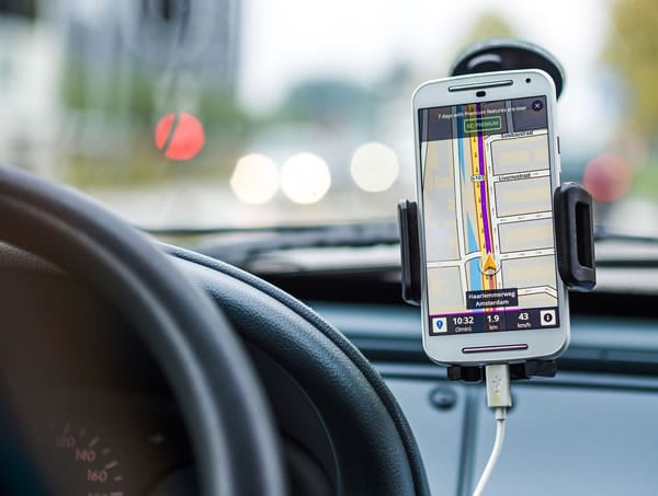 GPS tracking software shown on a mobile phone in a car