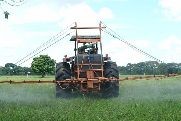 Tractor spraying chemicals to kill pests in field